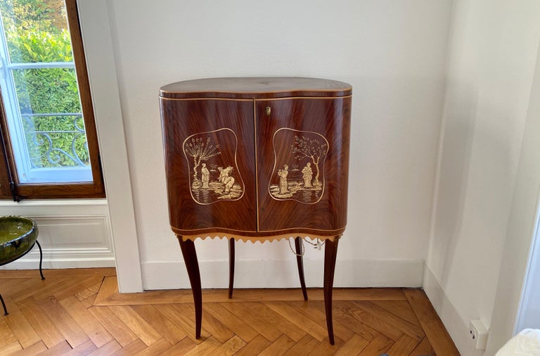 Attributed to Paolo Buffa, circa 1946. An elegant standing dry bar in walnut and birch wood with beautiful Asian decorations on both front doors. The inside of this beautiful cabinet is full of glass mirror parts which is very particular for the