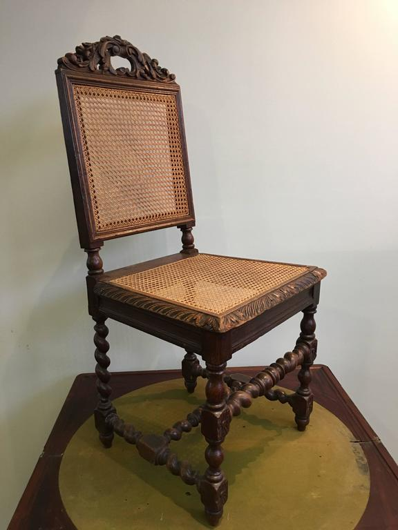 Set of four 19th century French carved walnut dining chairs in style of Louis Philippe. With hand-caned seats and backs. The chairs are raised on elegantly carved legs, France, circa 1830. Good condition.