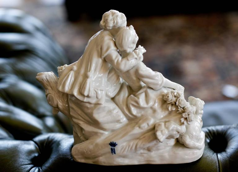 Biscuit porcelain 'Le Fluteur Boucher' circa 1751-1755,  Modeled after Boucher, representing a maiden seated on rockwork, in a talk with a gallant, supporting a basket of flowers, a lamb and dog at their feet.