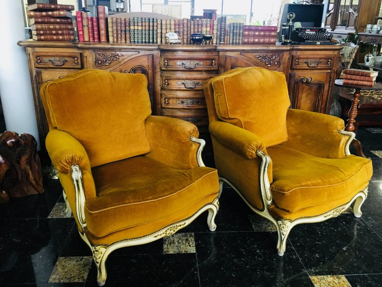 Splendid pair of 19th century French Louis XV lacquered bergeres. Having beautifully carved frame in acanthus leaf motif and mustard velvet upholstery. Perfect for today's stylish decors! France, circa 1870