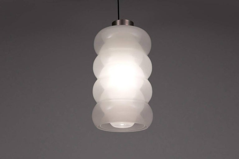 Designed by Carlo Nason in the 1960s this pendant lamp is a very good example of his work. The three layers of glass are creating a beautiful effect bringing some kind of deepness. The glass has no chips or breaks and the hardware is original to the
