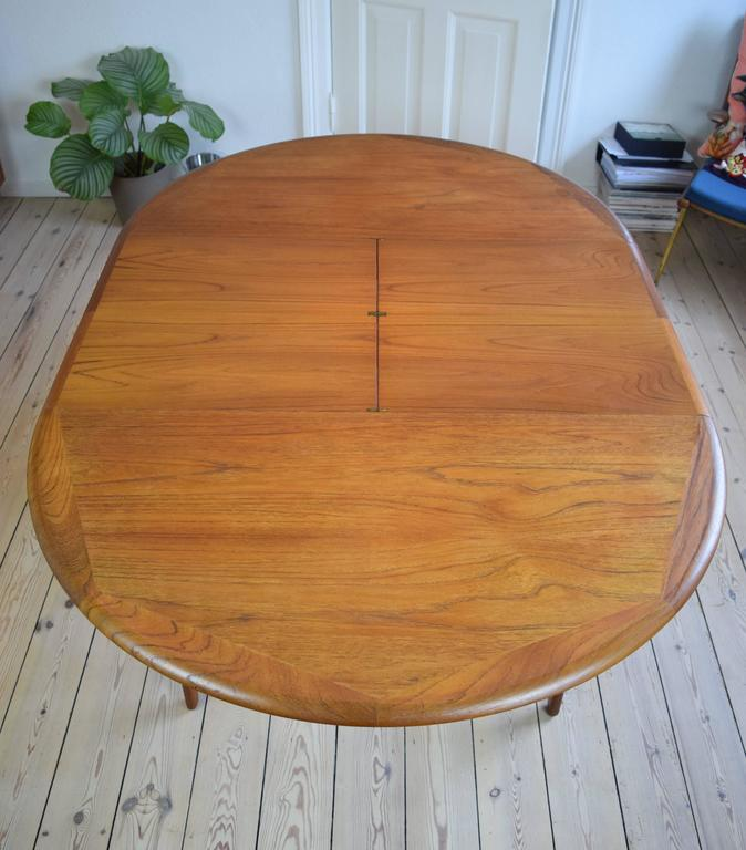 Rare teak dining table manufactured in Denmark in the 1960s. This piece was designed by Svend Aage Madsen and features two hidden plates which rotate on brass hinges to extend the table to 174cm to seat six-eight people. Wide matched grain on top