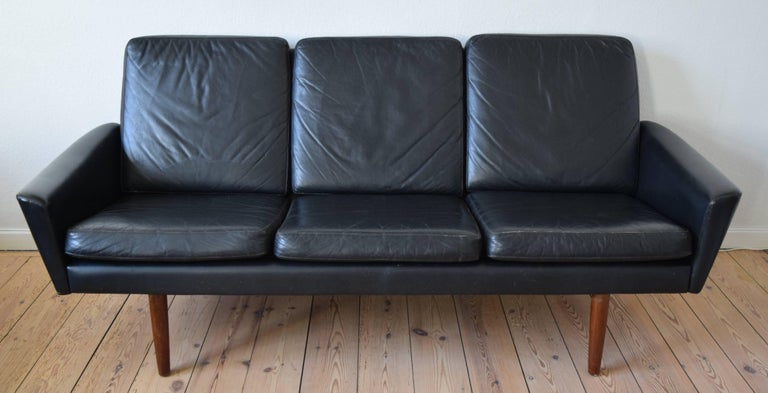 Leather three-person black sofa with teak legs manufactured in Denmark in the 1960s. The low slung design features angular lines and sits on solid teak legs. This is a genuine 1960s sofa in good condition with light wear for it's age. The sofa has