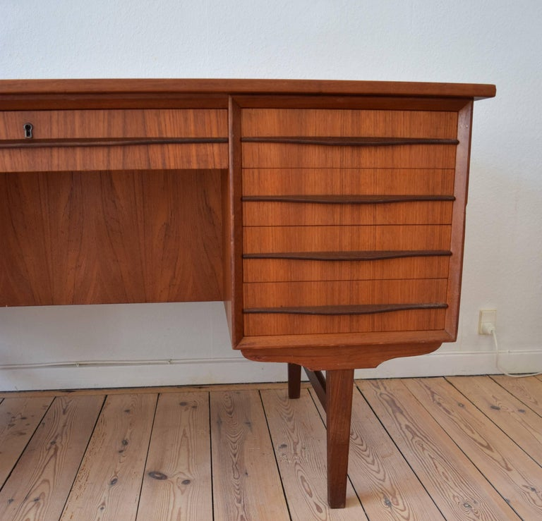 Teak executive desk manufactured in Denmark in the 1960s. Desk features seven drawers on the front, and bar cabinet and bookshelves on the back side. The full-length teak handles are unusual in that they sit on the centre of the drawer. Sits on