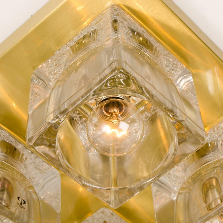 This sculptural vintage wall light consists of four clear glass cubes on a square brass frame which beautifully reflects the light with a warm glow. The four quality thick clear glass cubic shades have a Brutalist textured pattern at the bottom of