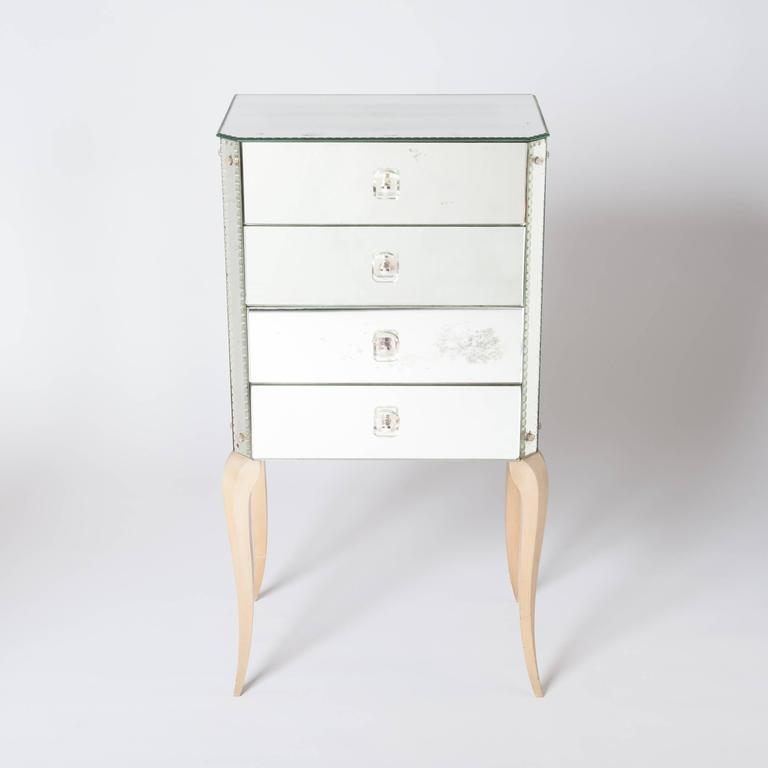Beautiful gracile mirrored chest with four drawers. A fine grinding covers the edges. The hardware under the decorative glass handles is silvered, the ivory colored legs shows already a fine craquele design.