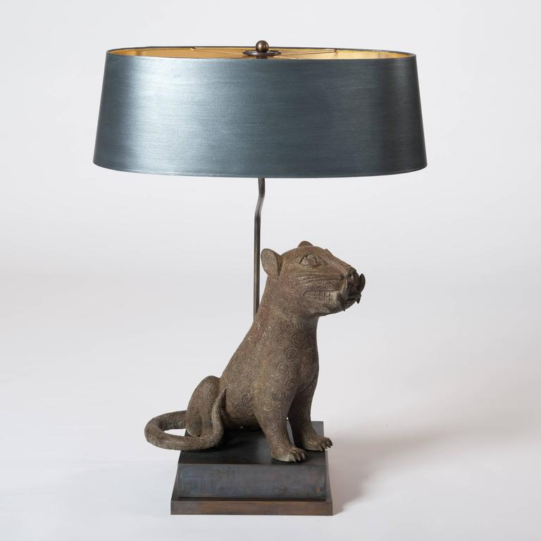 A very fine mid-century cast bronze from Benin arranged with a specially designed lamp construction and socle. The oval lampshade is hand-painted in anthracite-grey color with fine overlay in silver powder.