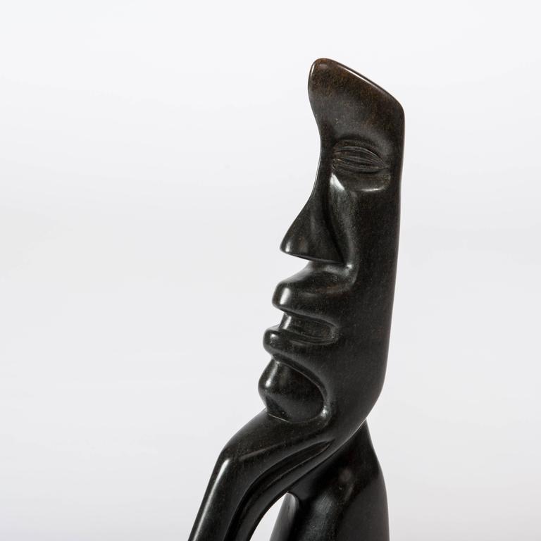 Cubistic shaped African figural black springstone sculpture by Bauden Khoreay on acryl socket. Measurements sculpture: 37cm x 5.6cm x 52.5cm Measurement acryl base: 30cm x 10cm x 2.5cm  Biography: Born in 1948 in Cholo, Malawi. Alongside
