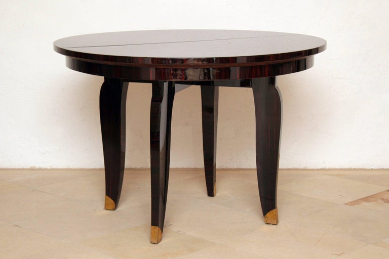 Elegant French Art Deco round dining table (extendable) or center table with wonderful warm and brilliant Macassar ebony veneer, four tapered Macassar wood legs with bronze trimming. Signed by stamp NANCY 1935 The grain of the Macassar veneered