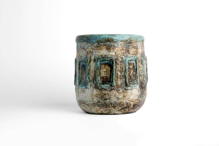 Large ceramic pot with blue, white and brown glazes. Geometric pattern around circumference of vessel.