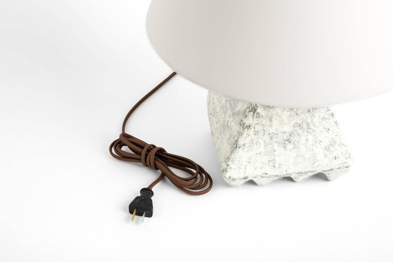The Cubetto lamp is 1 of 5 resin lamps of Dolatowski's cast lamp series. This resin lamp is organic, modeled and textured in finish and geometric in form.   Wired to US standards. Shade not included.  Influenced by his travels in Asia and the Middle
