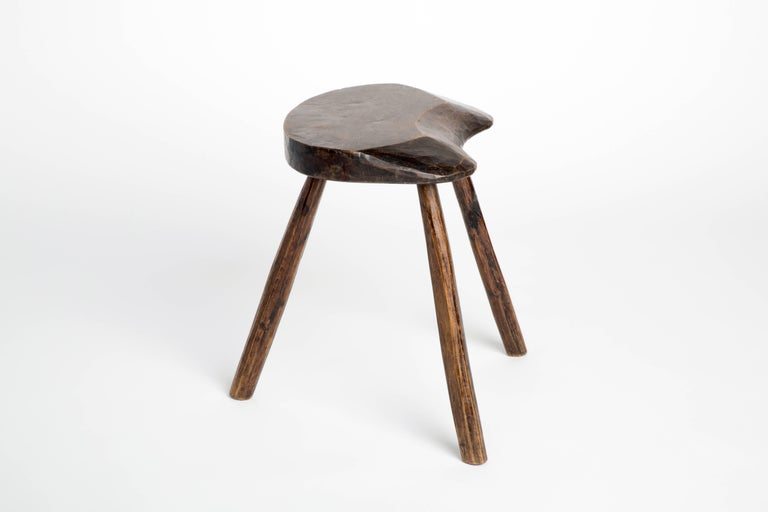 Solid and sturdy dark wood stool with three tripodal splayed legs.  Equally suitable for use as a small side table.