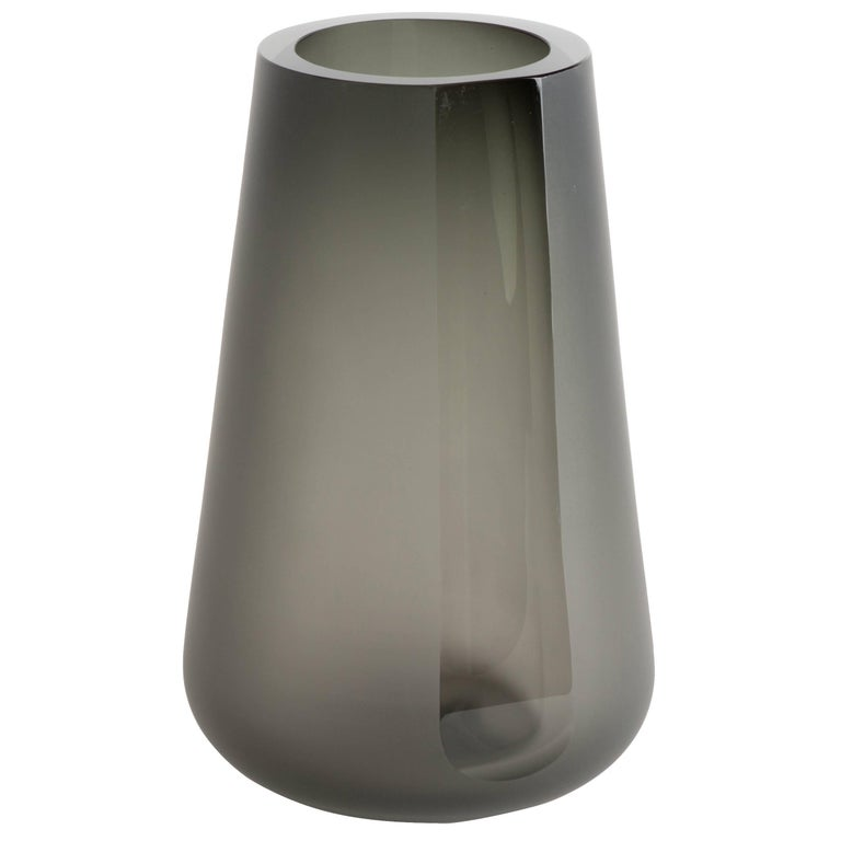 "The Porto vase extra large is a simple exercise in optics and color. The smoke grey color and reflective light are diffused by a surface etching. A single panel, or ""porto"" is carved and brought to an optical polish on the side allowing"