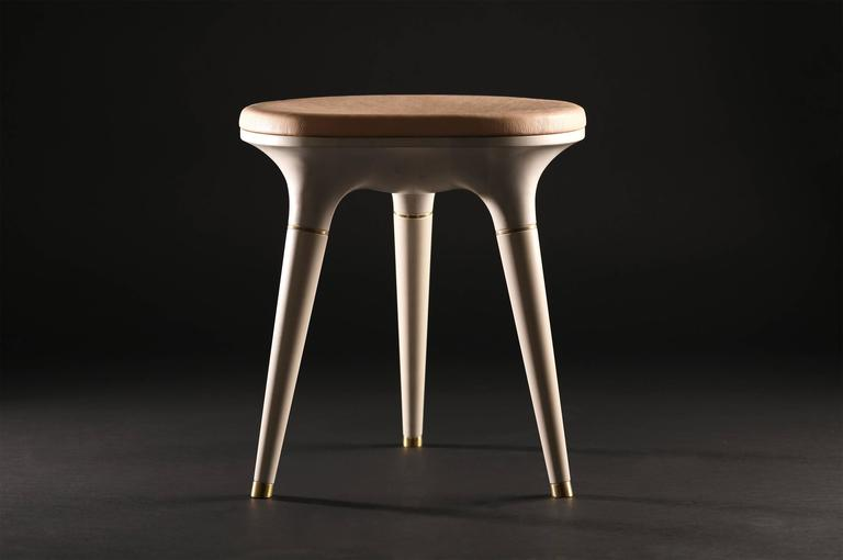 Bone Stool001 from Series 001 by Vincent Pocsik.  Carved maple stool with leather cushion top and brass accents. Shown here in a bone and natural vegetan leather top.  Vincent Pocsik finds the balance between old and new fabrication techniques