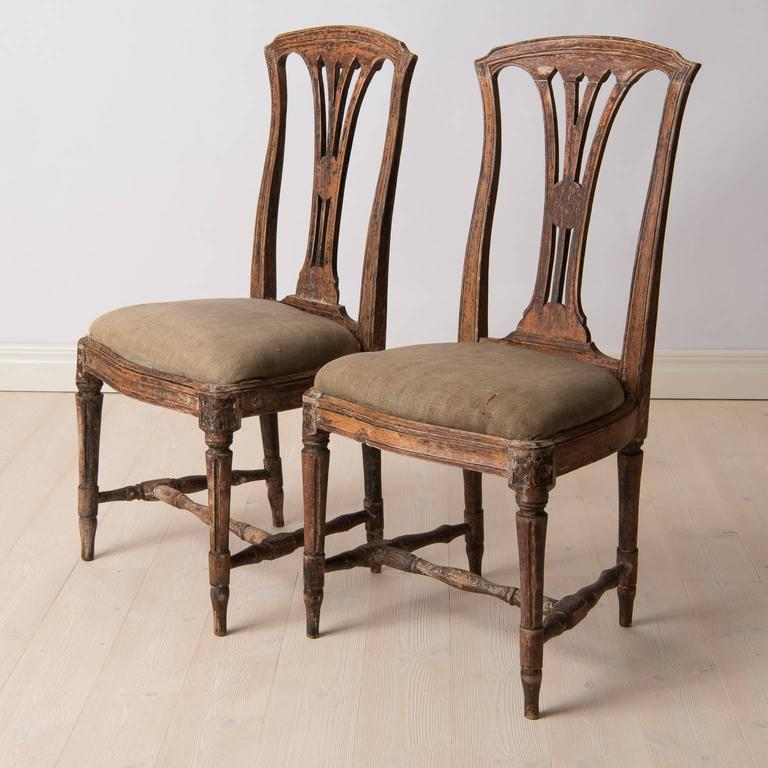 A pair of Gustavian chairs with traces of original paint. Both chairs are really nice quality as they are marked with Stockholm's Chair maker's official seal. Original seats and fabric from the 1770s. Seat height circa 48 cm.