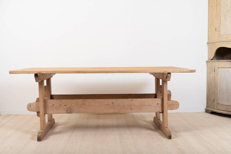 Trestle table from northern Sweden manufactured circa 1810. The table is in good condition and is complete. All parts are original to the table, even the four wedges are originals from the early 1800s; the condition is very good with whole and