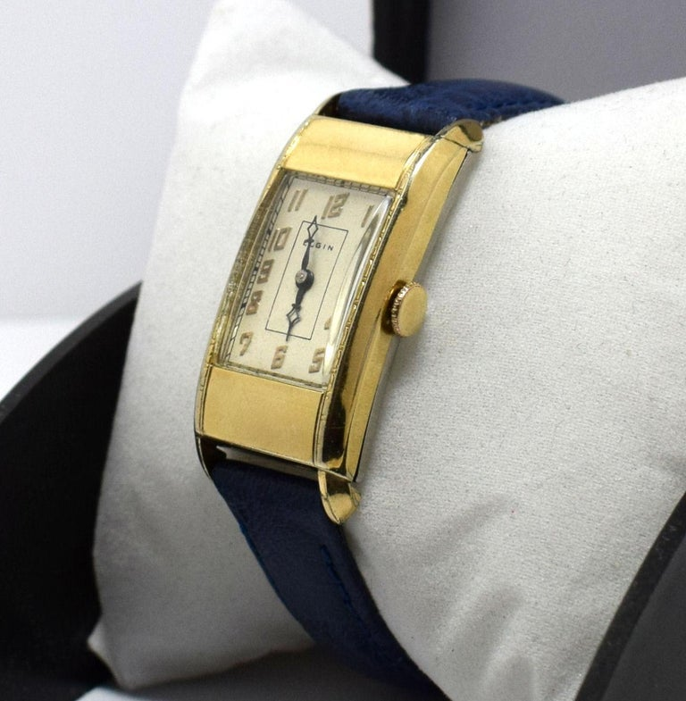 This is one of the finest examples of an Elgin Art Deco gents dress wristwatch we have seen in a long while. There is fine filigree etchings along both sides of the bezel. The timepiece is approx 25% longer than most of the watches of it's day which