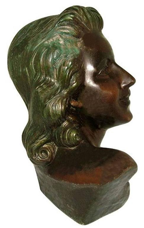 A really lovely French, Art Deco bust of very high quality. She's lifesize and shows the profile of a young Parisian woman with a victory roll hairstyle she excludes glamour. She's made from hollowed plaster and cold painted on top, wonderful bronze