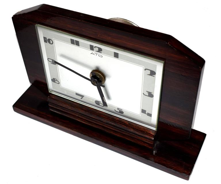 Superb 1930s Art Deco clock by the French clock makers ATO . The Macassar wood casing contrasting against the silvered dial and heavily stylised Art Deco numerals look nothing less than impressive, a clock that can't be mistaken for any other era. I