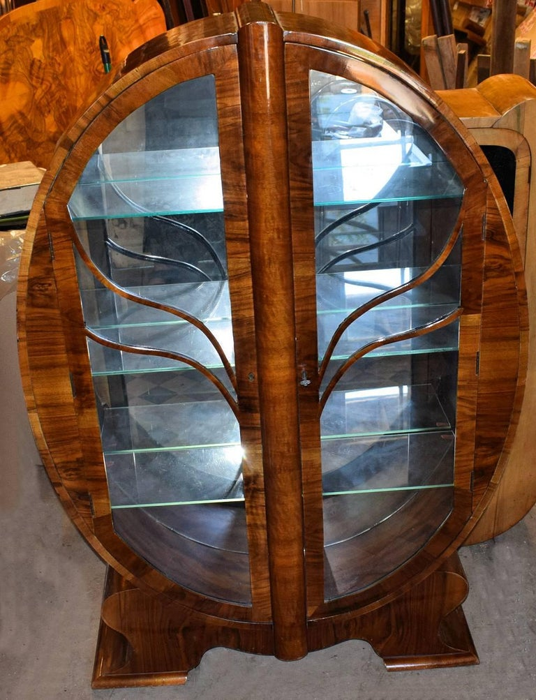 Very rare example of what is considered one of the more rare Art Deco display cabinets is this oval shaped heavily figured walnut veneered example. This particular one is even more scarce having still retained it's original mirror back, giving that