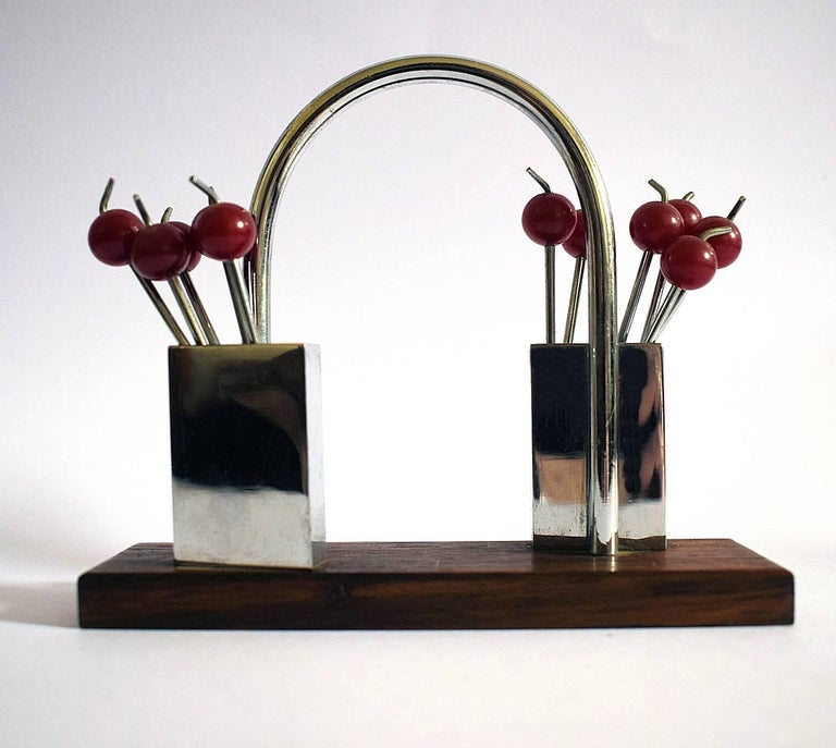 A charming 1930s, cocktail set originating from France. Features cherry red bakelite cocktail sticks with chromed metal prongs, all contained within two chrome boxed holders on a rosewood base. Great set in very good condition, minimal signs of age.