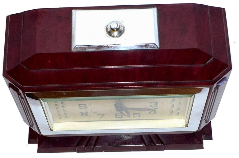 One of the more rare Bakelite French clocks we have in stock. This clock has a wonderful Bakelite case design. The bezel is mirror chrome, the Bakelite is a deep mottled red with flecks of black. A silvered dial and stylized Art Deco numerals finish