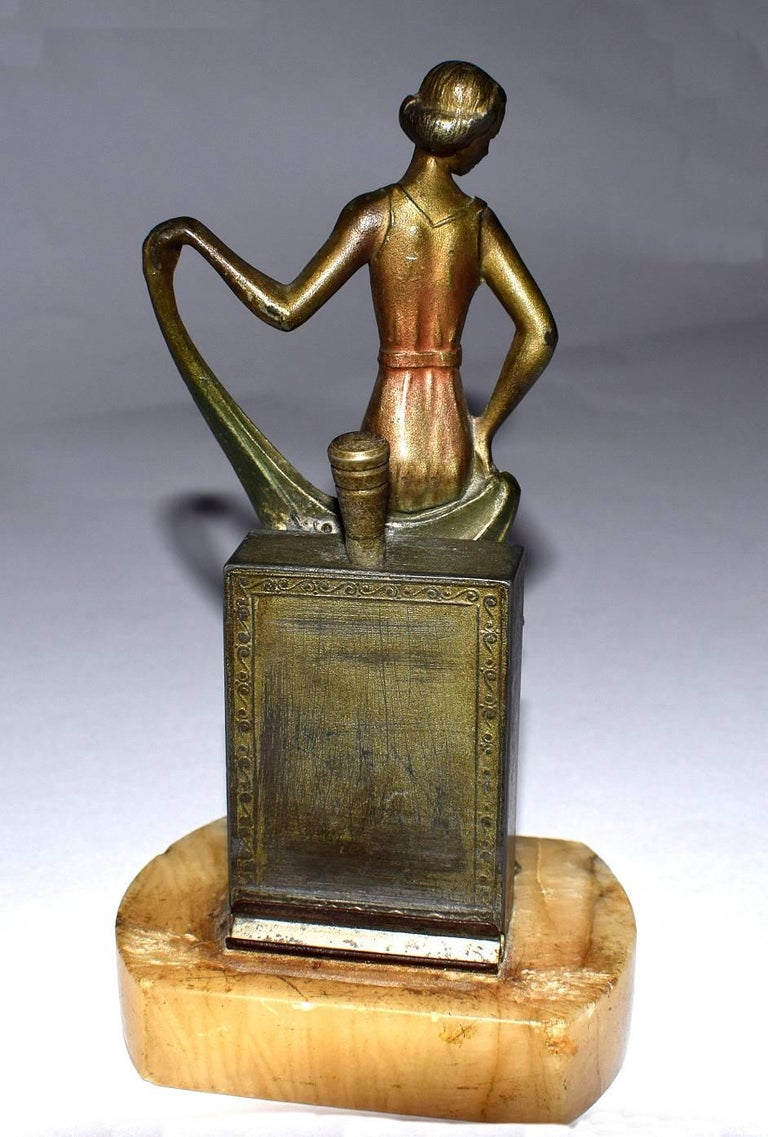 Delightful 1930s table lighter depicting a young lady. She's made from spelter and cold painted on top. Quite a weighty little item considering it's size. There is a dauber to the back and a recess resting area, not completely sure how it works but