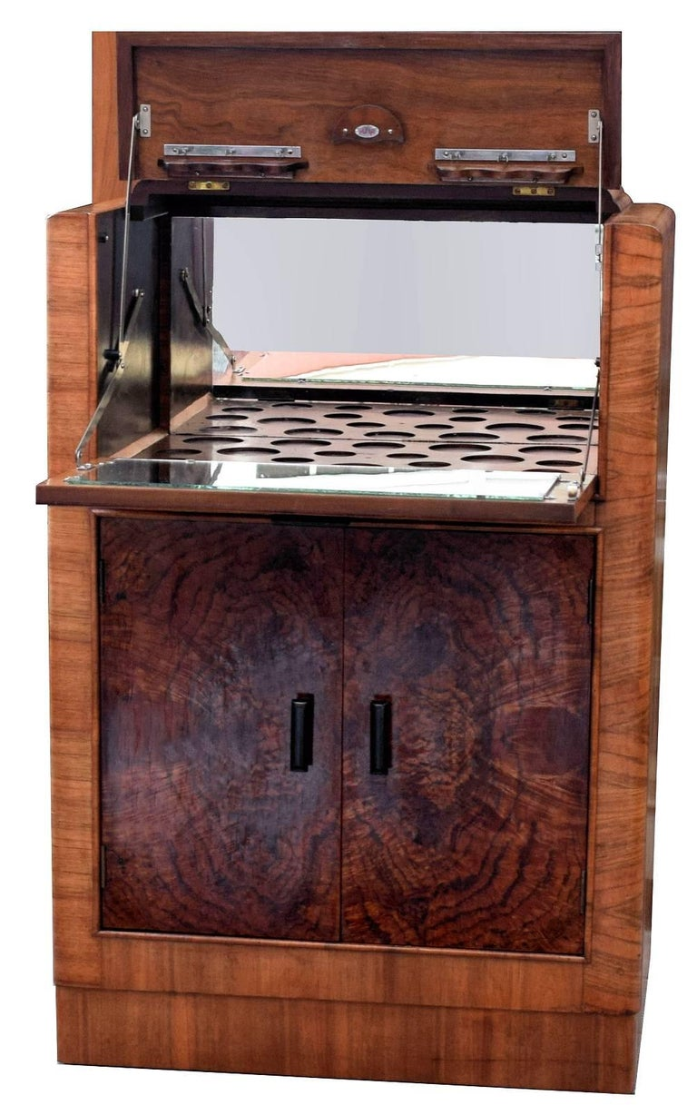 For your consideration is this stylish English Art Deco, 1930s figured walnut cocktail cabinet. This is a great looking period piece with exceptionally attractive walnut veneers. The drop down section at the top reveals a full mirrored interior with