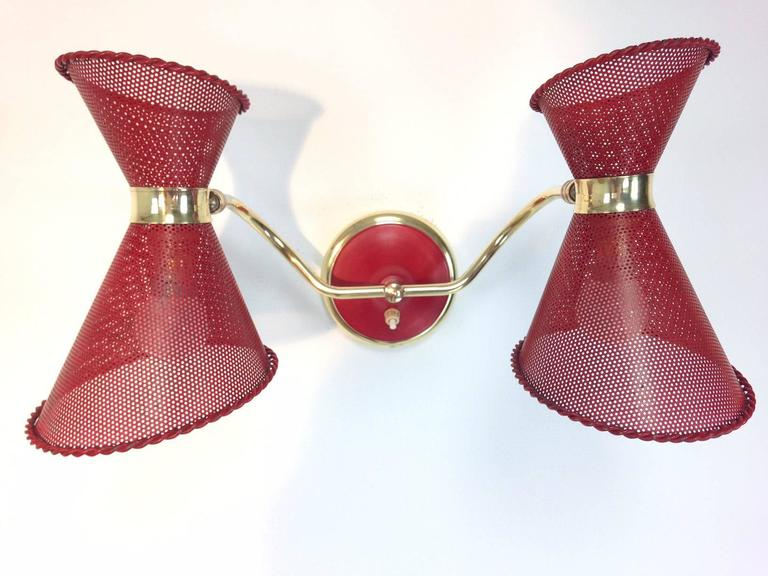 French wall light attrributed to Mathieu Mategot (1910-2001), produced by Atelier Mategot in the 1950s. The piece features rotatable, red varnished and perforated diabolo shades of metal, and is supported by brass arms and a plate. The width is