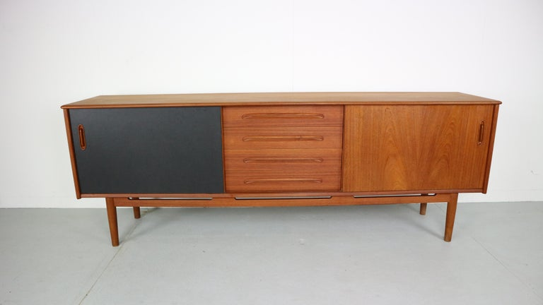 An absolutely wonderful and rarely seen 'Cortina' sideboard designed by Nils Jonsson and produced by Troeds of Sweden. Fantastic proportions and finished in a richly figured teak with contrasting black and teak sliding doors. Lovely detailing