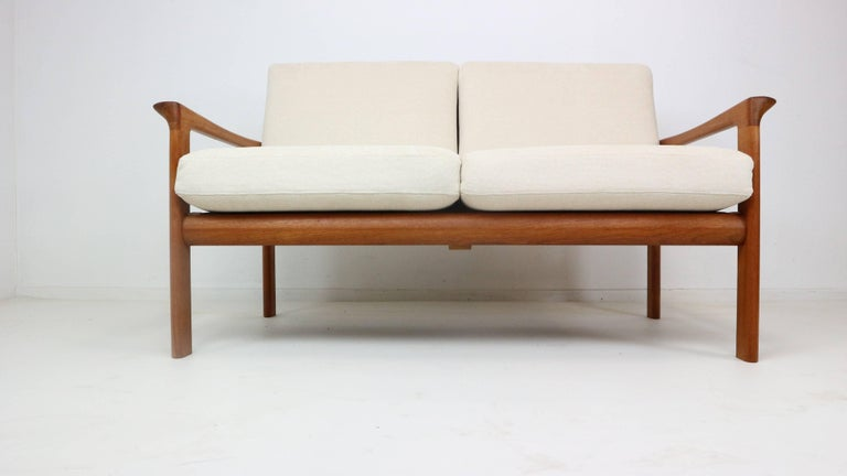 This 'Borneo' two-seat sofa was designed by Sven Ellekaer for Komfort, Denmark in the 1960s. It features a beautiful shaped solid teak frame with new of-white/light-beige upholstery and new webbing.