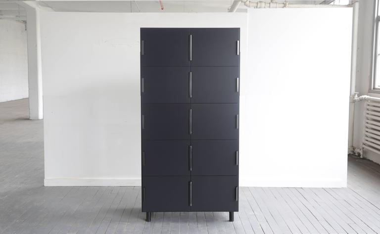 Nocturne is a multi-use storage cabinet with an austere beauty. Its center-hung doors swing inward on a shared hinge. The case is matte lacquered wood with blackened steel hardware. 
