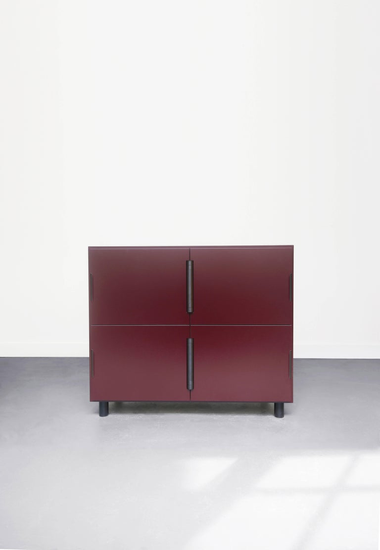 Nocturne is a multi-use storage cabinet with an austere beauty. Its center-hung doors swing inward on a shared hinge. The modern case is matte lacquered wood with sophisticated blackened steel hardware. 