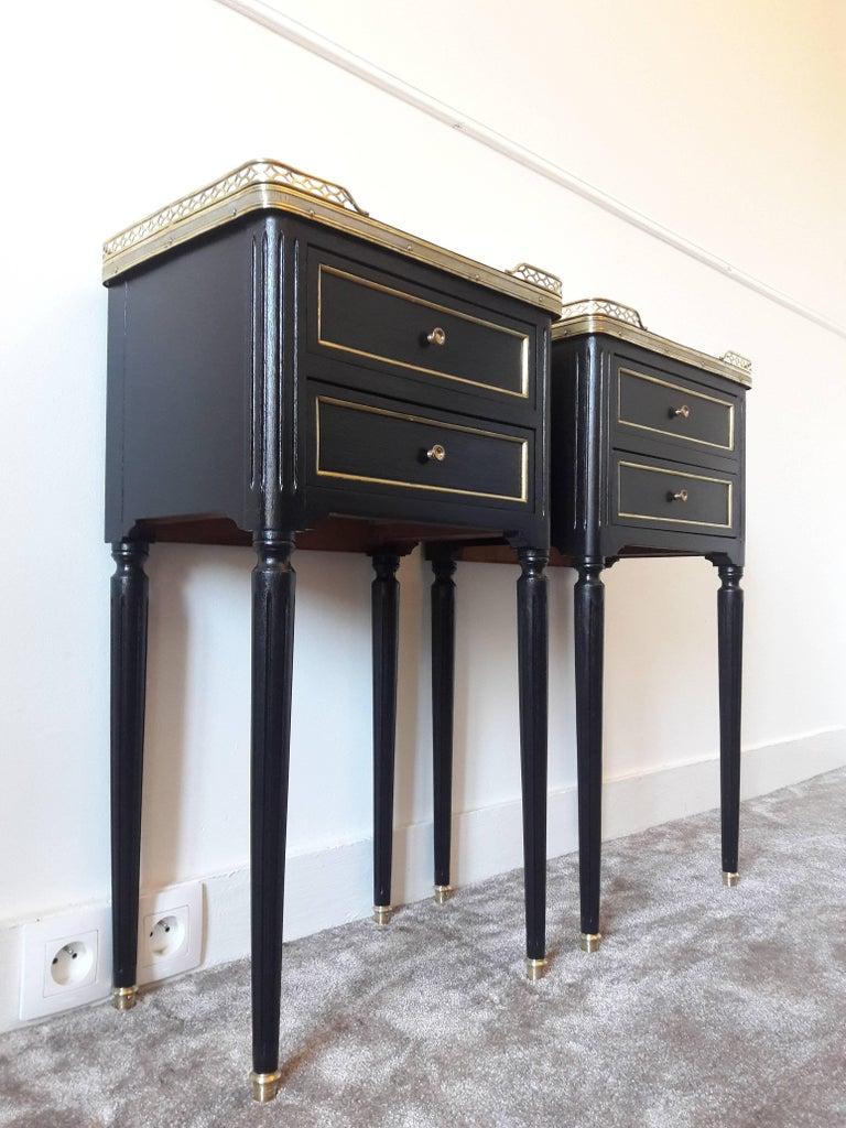 Antique French Louis XVI style pair of nightstands topped with a white marble, fluted legs finished with golden bronze clogs. Two dovetailed small drawers with brass details.