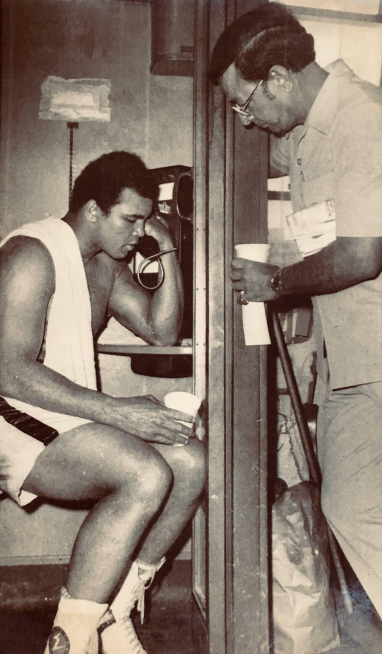 Muhammad Ali, vintage original press photo circa late 1960s-early 1970s. Photographed in Miami alongside noted Ali trainer Angelo Dundee and used as a press piece to announce Ali's forthcoming fight with Joe Frazier.  Measures approximately 6.5 x