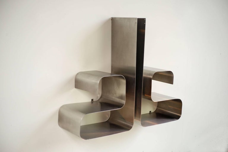 This pair of Zig-Zag shelves was designed by Joelle Ferlande & François Monnet for Kappa in France, circa 1970. They are made from smooth stainless steel frames and can be stood portrait or horizontal.   Bibliography: