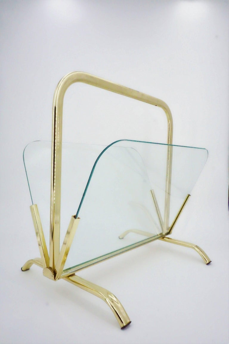 Glass And Brass Magazine Rack in Hollywood Regency style. Elegance and transparency for this superb gilt metal magazine rack and glass wall. All in excellent condition!