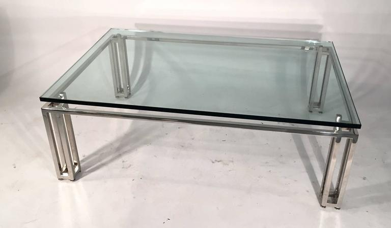 Chrome base coffee table with a floating glass top.