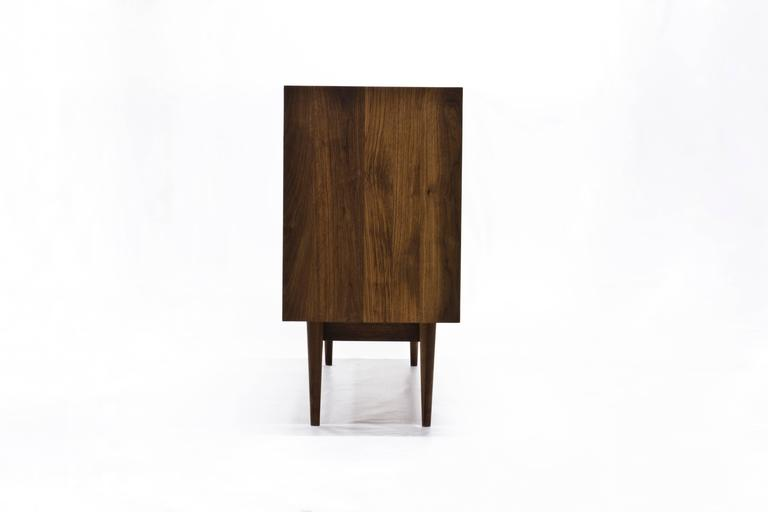 The Sine Wave console by Michael Dreeben for Wooda is a bespoke-quality solid walnut cabinet. The sine waves that ornament the door panels function most immediately as a decorative element. But they also emit the LED light from within the cabinet