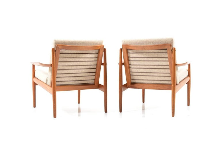 Early Danish pair of easychairs in teak. Designed by Arne Vodder. Manufactured by Glostrup. Original cushion in creme/sand wool fabric. 1950s. production
