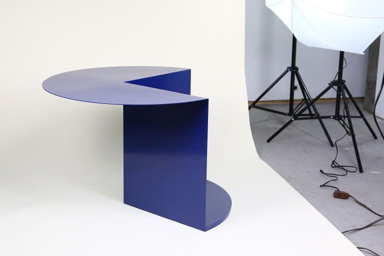The coffee/side table consists of only necessary parts. The top panel functions as the surface of the table. The two vertical panels and the bottom surface create support for the table and suggest a space for the storage or display of personal