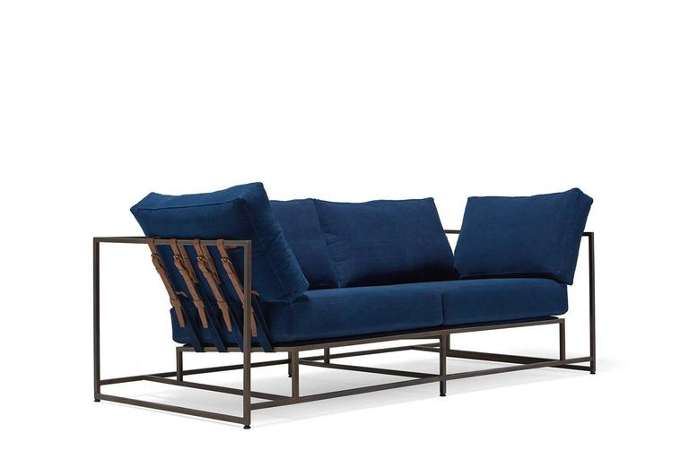 Inspired by a worn-in pair of jeans and created alongside the team at Simon Miller USA, this two seat sofa has naturally dyed indigo cotton canvas upholstery atop an antique copper frame with indigo webbing and cognac leather supporting belts. Each