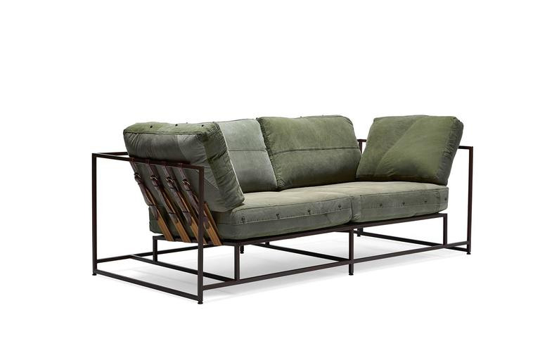 The inheritance sofa in a slightly smaller size. This sofa features a minimal, stripped-down design concept and vintage olive green military canvas upholstery atop a steel frame with a marbled rust finish. The supporting belts are composed of a tan