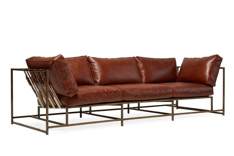A new sofa in our leather series, this version of the Inheritance Collection sofa has a rich Walnut leather upholstery atop an antique brass steel frame with natural cotton webbing, matching walnut leather belts, and antique brass buckles.