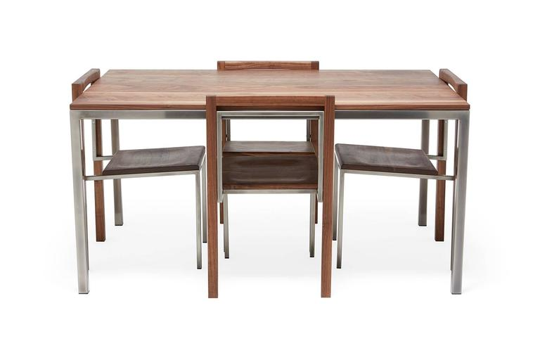 Dining goods are one of the newest additions to Stephen Kenn's The Inheritance collection. A solid walnut and steel dining table with simple and modern lines, with a set of four matching chairs.  This item is made to order in Los