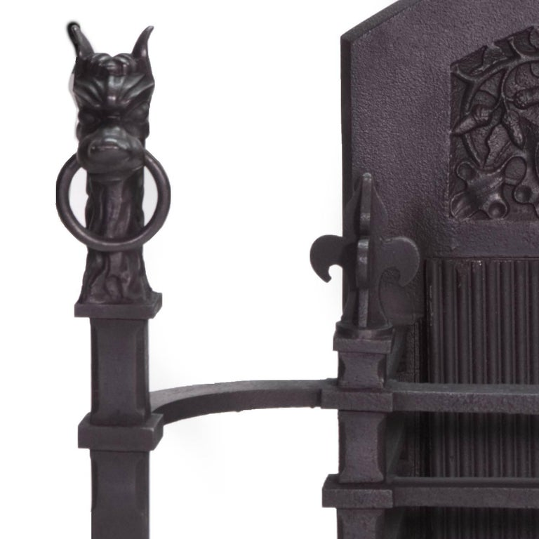 A very powerful antique cast iron Victorian black Gothic fire basket.  With Very Unique Andirons as stylized griffins with rings through their noses  and Medieval Styled fire back.  Measures: Back width 22 1/2 (57 cm) Back height 28 1/4