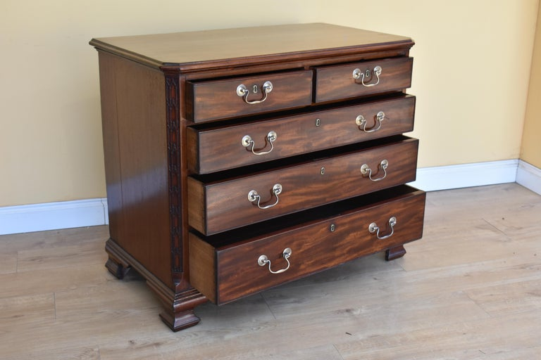 For sale is a top quality 18th century George III mahogany chest of drawers with canted corners with decorative blind fretwork. The chest has wonderfully graduated drawers, two short over three long. Each drawer has brass swan neck handles and