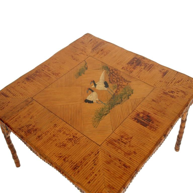 Fabulous Art Deco bamboo lacquered table with top covered with bamboo strips. The top of the table is decorated in the middle with a lacustre scene with inlaid two Japanese birds.