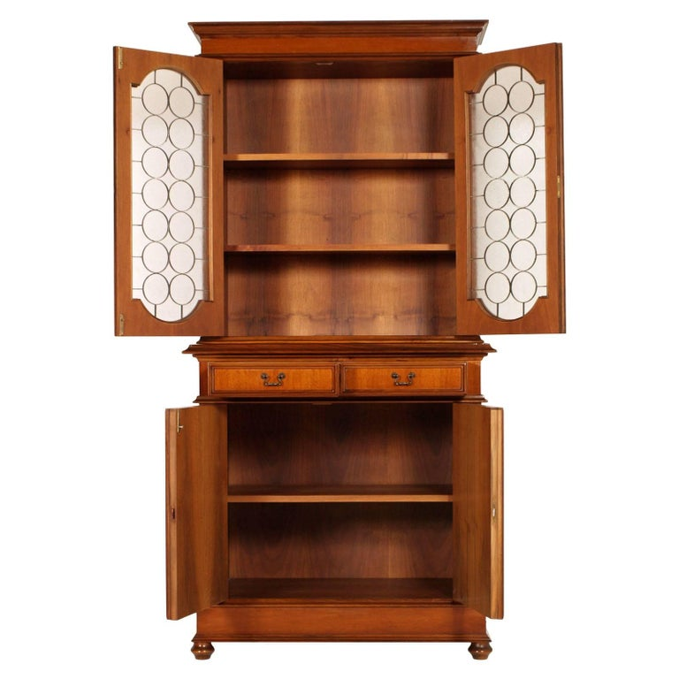 Italian bookcase period 1930s in walnut and walnut veneer with two drawers, wax polished. Upper showcase with grating and the two lower doors covered in leatherette. Excellent conditions.  Measures cm: H 106/206, W 102, D 50.