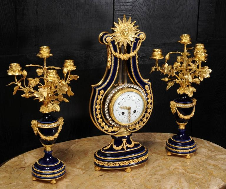 Antique French clockset, one of the nicest Louis XVI designs, elegant lyre shape in cobalt blue Sevres style porcelain mounted with exquisite ormolu (finely gilded bronze doré).